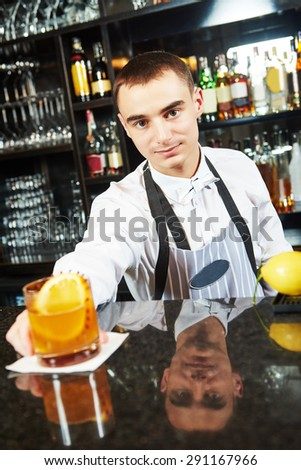 young barman worker at bartender desk in restaurant bar with coctail - stock photo