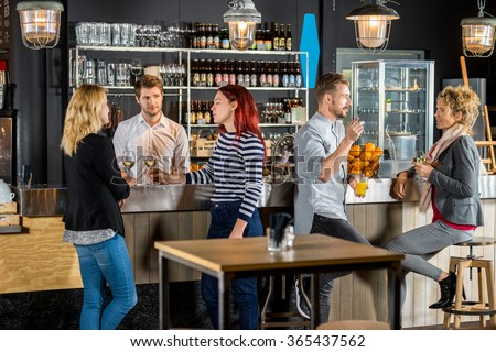 Young bartender with customers talking and having drinks in bar