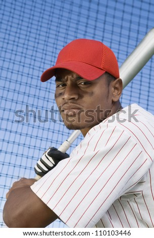 Young baseball player batting against net - stock photo