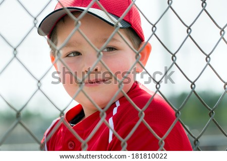 Young baseball player in uniform sitting in dugout - stock photo
