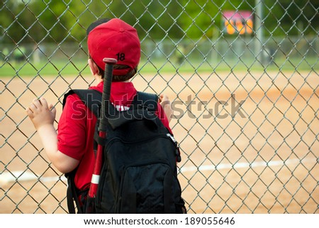Young baseball player watching game from outside fence - stock photo