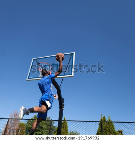 Young basketball player drives to the hoop for a high flying slam dunk in front of a clear blue sky with copy space for your text. - stock photo