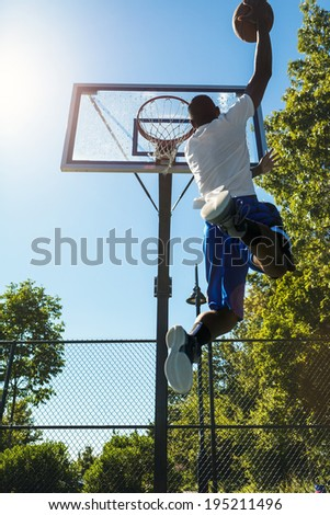 Young basketball player drives to the hoop with a high flying slam dunk. Slight lens flare. - stock photo