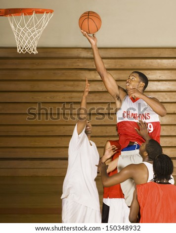 Young basketball player dunking basketball in hoop - stock photo