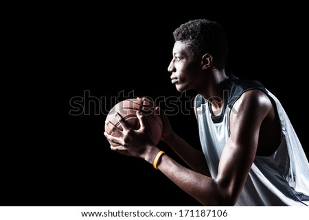 Young basketball player isolated on black background - stock photo