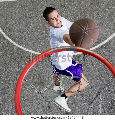 Young basketball player on the street going  to the hoop. Great angle from above. - stock photo