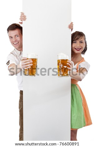 Young Bavarian man and girl in dirndl with ad space and beer stein. Isolated on white background. - stock photo