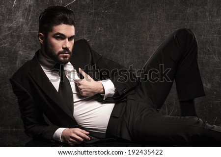 young bearded business man pulling his collar while resting on the floor