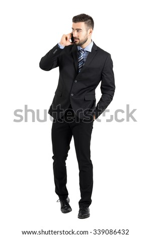Young bearded businessman in suit talking on the phone walking towards camera looking away. Full body length portrait isolated over white studio background.  - stock photo