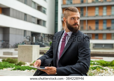 Young bearded businessman sitting on a bench and using tablet pc. Outdoor photo - stock photo
