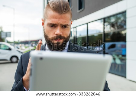 Young bearded businessman using his tablet pc. He is surprised. Outdoor photo - stock photo
