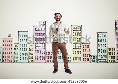 Young bearded Caucasian man in casual clothes with headphones and phone is showing a thumb up gesture on white background with colorful buildings drawn on it - stock photo