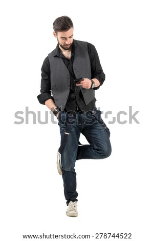 Young bearded guy scratching rubbing legs while on smartphone. Full body length portrait isolated over white background.  - stock photo