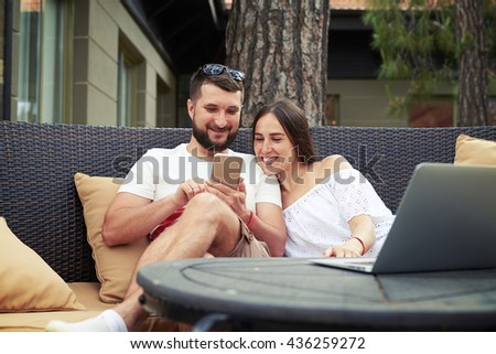 Young bearded man and smiling beautiful woman are sitting relaxed on cozy couch on open terrace and watching something on man's phone - stock photo