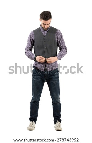 Young bearded man buttoning waistcoat looking down. Full body length portrait isolated over white background.  - stock photo