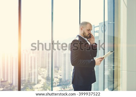 Young bearded man entrepreneur is phoning via mobile phone and studying the norms and documents of an international organizations via digital tablet.Businessman is standing near window with copy space - stock photo