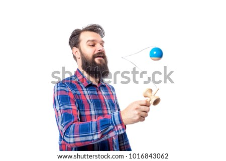 young bearded man playing with kendama on white background