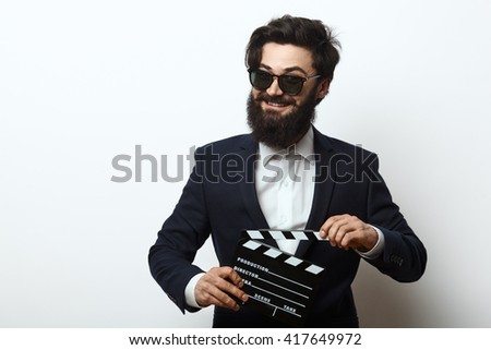 Young bearded man wearing sunglasses and black suit. Movie director holding a clapperboard isolated on white background with copy space - stock photo