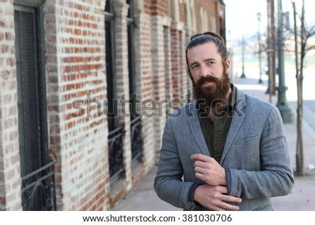 young bearded man with man bun and a very nice and clean skin with copy space on the left side of the photography - stock photo
