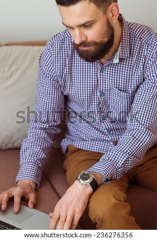 Young bearded man working on laptop at home - stock photo