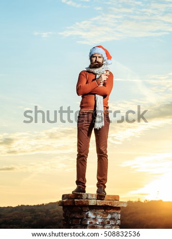 young bearded santa claus man with long beard in red sweater pants and new year hat in scarf with glass of champagne drinking and celebrating christmas or xmas on sunny blue sky on brick chimney