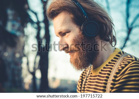 young bearded stylish handsome hipster man listening music with headphones outdoors - stock photo