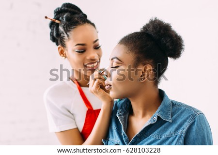 Young beautiful African American woman applying make-up by make-up artist