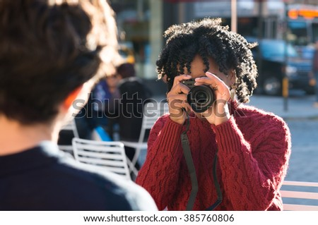 Young beautiful african woman taking photos of her boyfriend. Attractive young black girl taking a picture with a digital camera. Portrait of a woman photographer clicking a photo to remember.  - stock photo