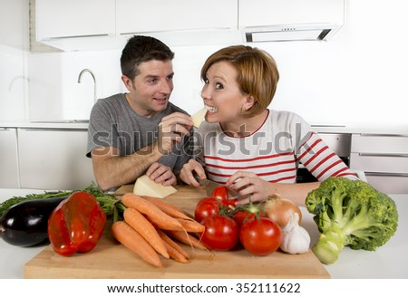 young beautiful American couple working at home kitchen  preparing  vegetable salad together smiling happy in husband and wife cooking team and  healthy fresh food concept