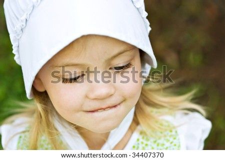 Young beautiful Amish child in bonnet.