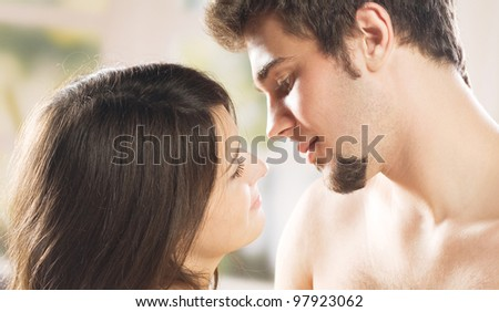 Young beautiful amorous couple at bedroom - stock photo