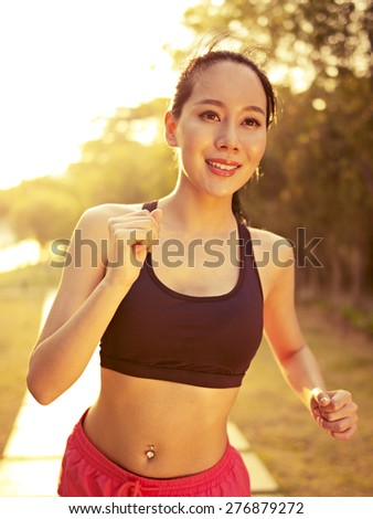young beautiful and fit asian woman running jogging outdoors in park at in warm sunlight, fitness, sport and exercise, healthy life and lifestyle concept. - stock photo