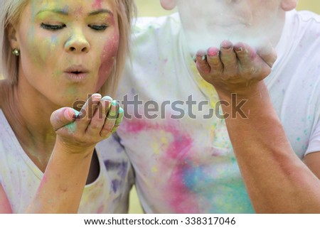 Young Beautiful and funky couple playing with coloured water paint powder on the Holi Festival - stock photo