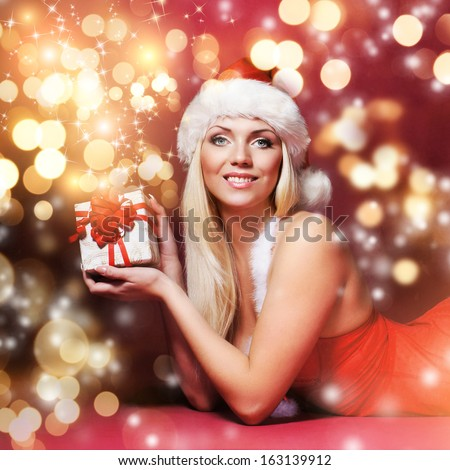 Young, beautiful and happy girl with the Christmas present over the glowing winter background - stock photo