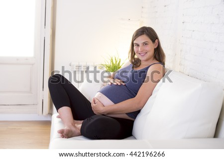 young beautiful and happy 8 or 9 months pregnant woman sitting at home living room couch holding big belly with her hands in pregnancy and motherhood or parenting concept - stock photo