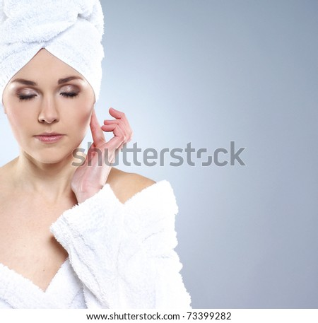 Young, beautiful and healthy young woman in bath clothes over grey background