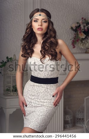 Young beautiful and sexy woman posing in white dress in white interior. Fashion vogue style portrait of stylish sexy sensual girl with long curly brunette hair and head jewelry - stock photo
