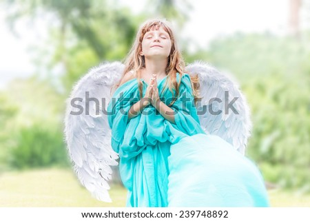 young beautiful angel child girl on natural green background - stock photo