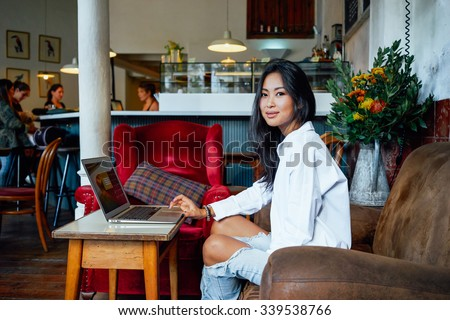 Young beautiful Asian business woman at a coffee shop working on a laptop - stock photo