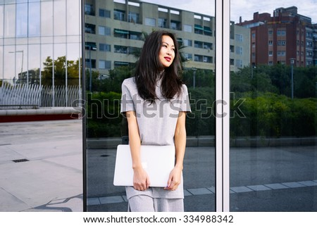 young beautiful Asian businesswoman posing with her laptop on a background of a mirror wall of a skyscraper