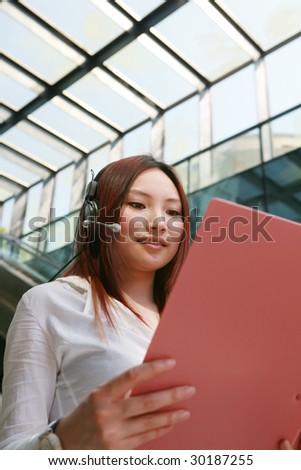 young Beautiful asian Customer Representative holding with folder - stock photo