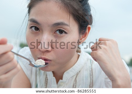 Young beautiful asian girl eating food (selective focus)
