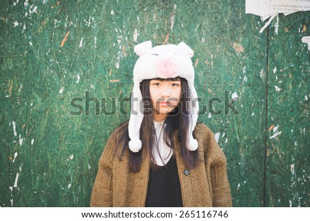 young beautiful asian hipster woman in the city - wearing funny piggy winter cap - stock photo