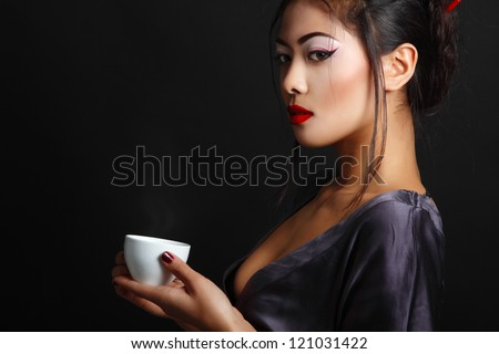 Young beautiful asian woman and tea ceremony, studio shot over black background with copyspace - stock photo