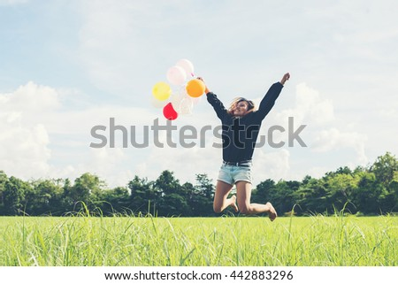 young beautiful asian woman holding balloon on green grassland running and jumping enjoy fresh air - stock photo