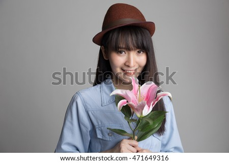 Young beautiful asian woman holding lily flower in her hand