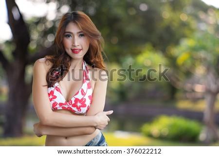 Young beautiful Asian woman in red bikini with short pants jean, voluptuous posing outdoors  - stock photo