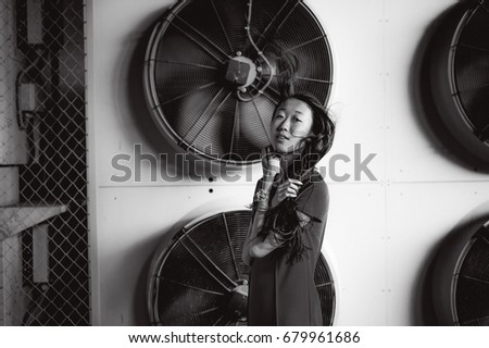 Young beautiful asian woman, on the background of industrial air conditioning system fans. Portrait of a girl with flying hair