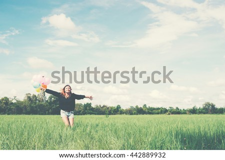young beautiful asian woman running and jumping on green grassland with colored balloons enjoy fresh air - stock photo