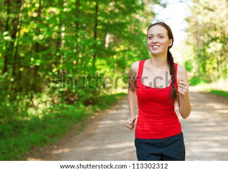 Young beautiful athlete woman jogging outdoors in park